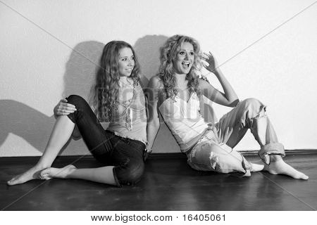 Two attractive young  girls sitting close on hardwood floor in home smiling and laughing.