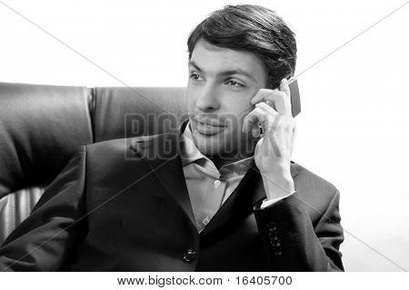 Retrato de primer plano de un exitoso empresario guapo hablando por teléfono celular. Sobre fondo blanco