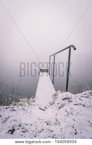 Snowy Footbridge With Metal Railings Near The Pond