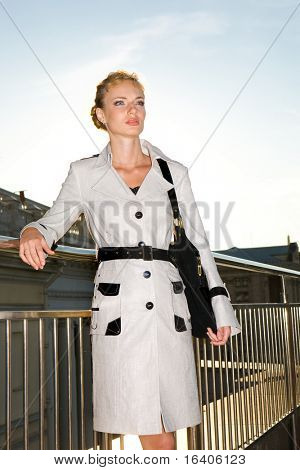 Beautiful Young Woman in light raincoat