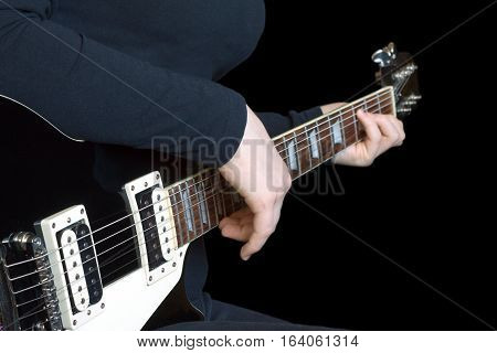 Girl musician plays rock on black six strings electric guitar. Photo isolated on black background