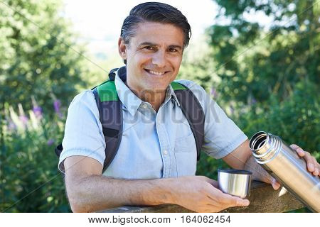 Mature Man Pouring Hot Drink From Flask On Walk