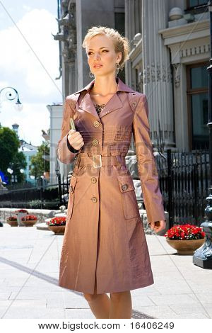 Beautiful Young Woman in brown raincoat. Against  backdrop of building