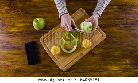 Young girl peeling green apple with peeler