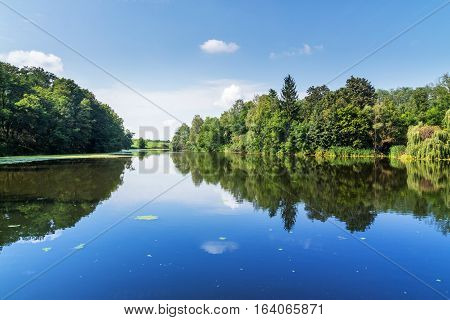 Summer rural landscape. Trees and sky reflected on the surface of a pond. Nature photography. Czech republic