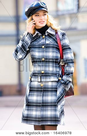 Beautiful young blond in a coat talks on phone. Photography for fashion brand Catalog clothes