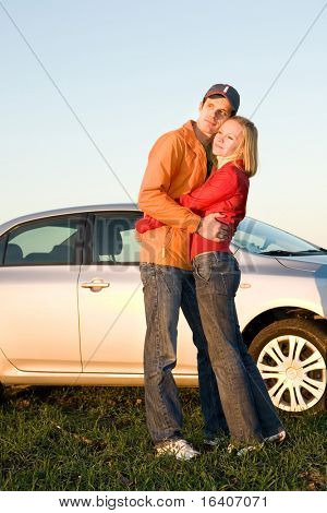 Happy young couple with their new car