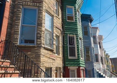 facades of typical american townhomes with front stairs in jersey city