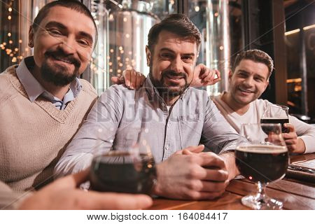 Saturday night. Handsome cheerful male friends sitting together at the table and smiling while looking at you
