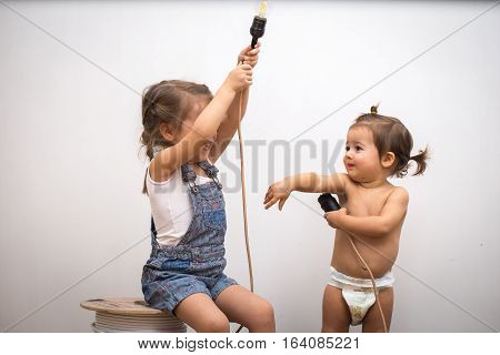 Two Little Girl With Light Bulb In Hand