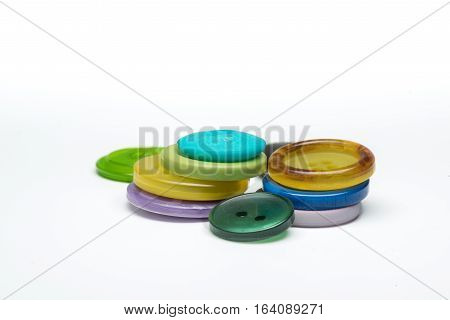 Pile of colorful sewing plastic buttons on white background
