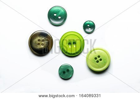 Collection of six sewing buttons on white background