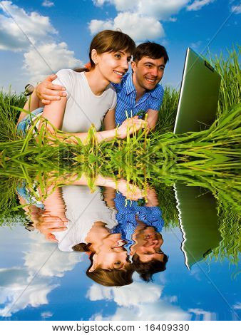 Casal feliz ocasional em um computador laptop ao ar livre. Coloque sobre a grama verde.