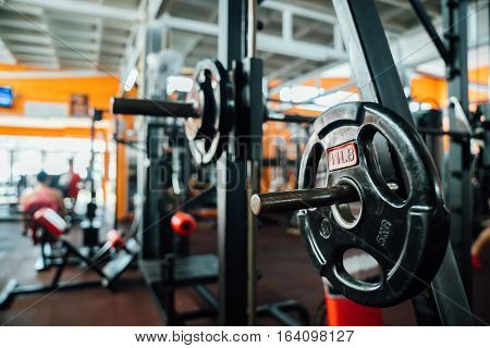 Interior gym with sports equipment. The bar with dumbbells in focus. sports background. Barbell ready for workout.