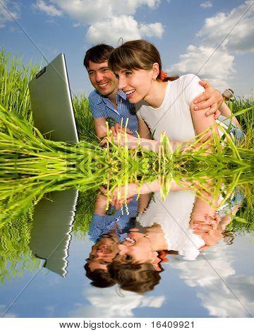 Casal feliz em um computador laptop ao ar livre. Coloque sobre a grama verde.