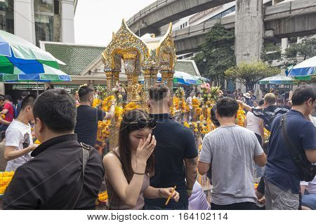 BANGKOKTHAILAND - DEC 31 : snapshot of crowd worship in Erawan shrine at ratchaprasong area on december 31 2016 Thailand. there are many tourist worship at Erawan shrine in new year festival