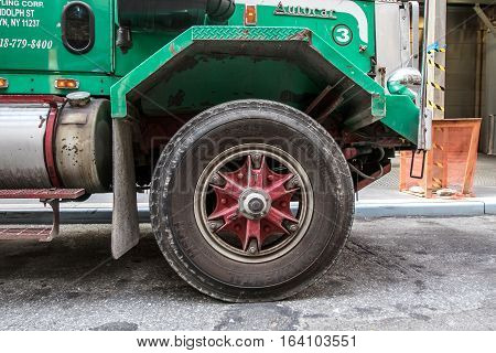 New York August 2 2016: A front wheel of a large garbage truck.
