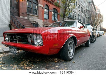 New York, November 28, 2016: A classic red 1973 Ford Mustang Sportsroof is parked in the street in Manhattan.