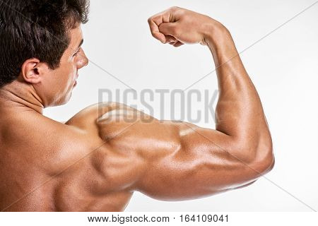 Strong bodybuilder man with perfect shoulders biceps triceps
