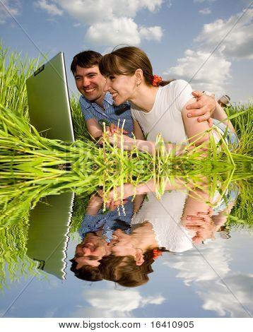 Casual casal feliz no computador portátil ao ar livre. Coloque sobre a grama verde