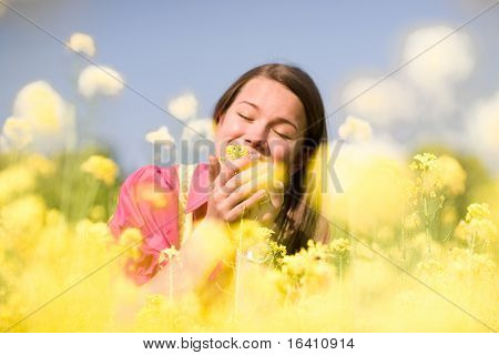 Pretty smiling girl relaxing on green meadow full of yellow flowers. Soft focus. Focus on eyes.