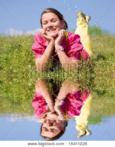 Pretty smiling girl relaxing on green meadow full of flowers. Soft focus. Focus on eyes. Reflected in water