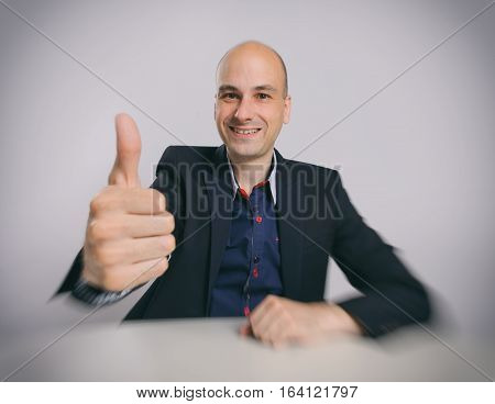bald guy sits at the desk with thumbs up