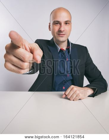 serious bald guy pointing finger at you
