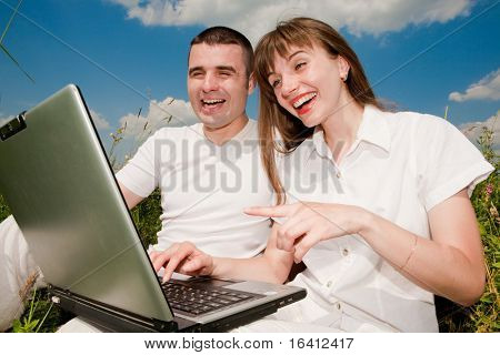 Casual happy couple on a laptop computer outdoors