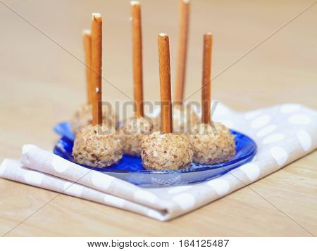 Cheese bites. Cheesy appetizer decorated with ground nut and pretzel sticks. Party food.