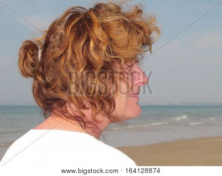 Profile Portrait Of A Senior Woman On The Beach Enjoying Retirement