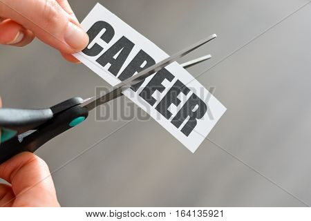 Career interruption concept with woman hand cutting with scissors