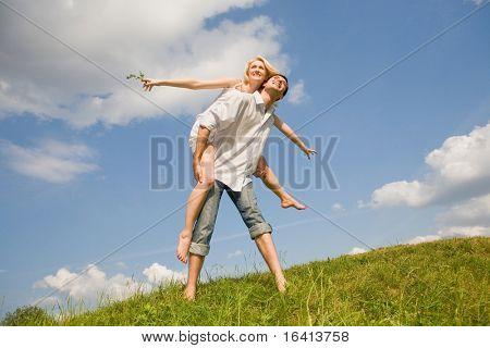 Jovem feliz amor par - saltando sob céu azul