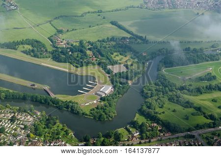 Aerial view of the River Thames as it bends between Eton and Windsor with the renowned rowing venue Eton Dorney Lake to the left and part of Windsor Racecourse to the right. Slightly cloudy summer morning.