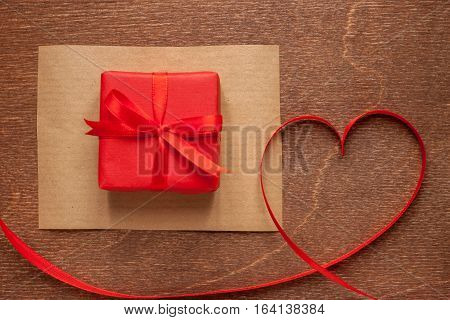 heart of red tape and gift box on wooden background