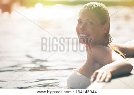 Enjoy the summer. Woman relaxing in the pool water. A beautiful woman with big smile in water in a swimming pool. Relaxation and peace. Against the side of the pool. Intense summer lights. Wellness enjoyment in the summer.