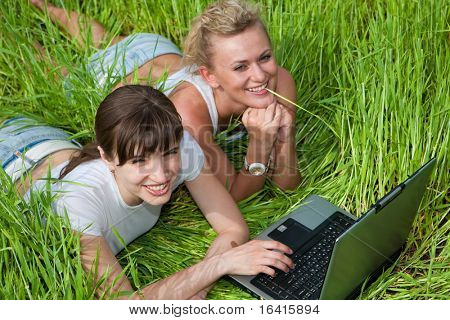 Two beautiful girls in white clothes are laughing and looking at laptop computer outdoors. Lay on the green grass.