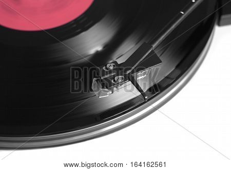 Rotation black vinyl record with red label on turntable player in silver case. Horizontal photo top view closeup