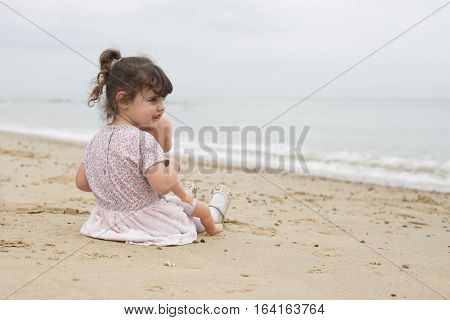 Toddler Sitting On Beach With Her Dolly