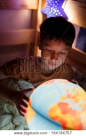 Little boy discovering countries on globe at night studying in bed