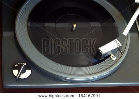 Old vintage record player playing black flexible disc. Horizontal top view closeup