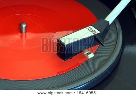 Old vintage record player playing red flexible disc. Horizontal top view closeup