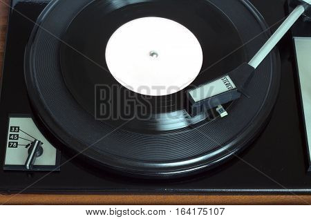 Old vintage record player playing vinyl record with pink label. Top view horizontal photo view