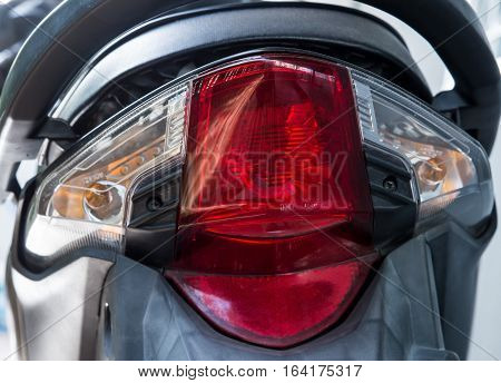 Red rear light of the modern motorcycle in the garage.