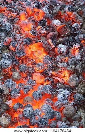 A smoldering coal fire. Bright background of black and red colors. Vertical.