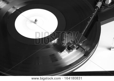 Modern record player with magnetic stylus in silver case playing a vinyl record with white label. Horizontal photo top view closeup