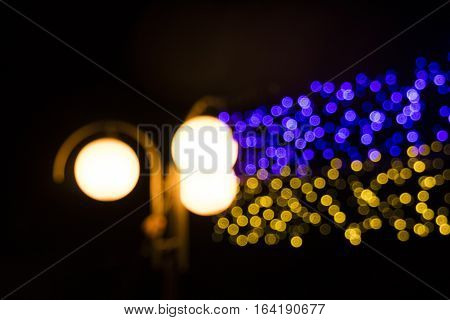 colored lights blur as bokeh in blue and yellow colors
