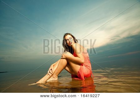 Beautiful girl sitting on water