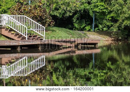 Abandon and broken jetty with reflection in the lake.