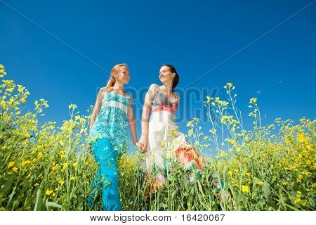 Two beautiful girl in white clothes go to the yellow flowers